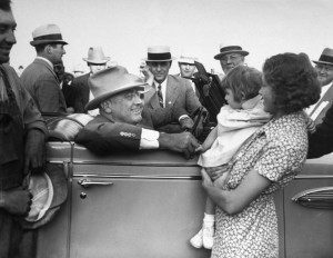 President Franklin D. Roosevelt talks to a young mother while sitting in his car during a trip to the western U.S. in January 1936